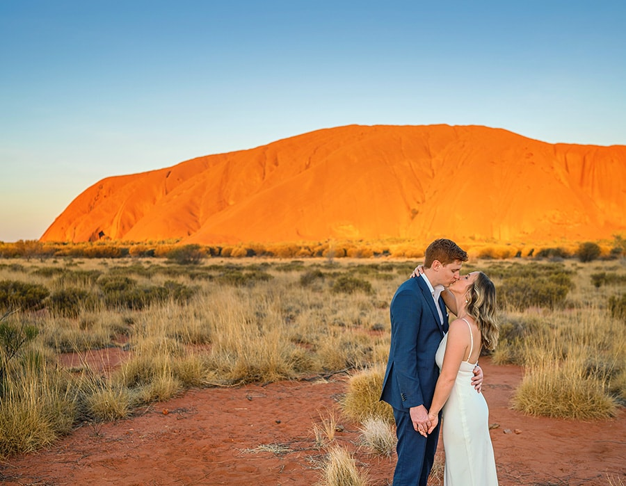 bride and groom in front of uluru at sunset